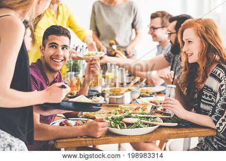 Smiling people enjoy fresh dinner at communal table in restaurant with organic food