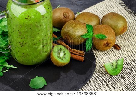 A colorful close-up of a glass jar of kiwi yogurt and healthy ingredients on a fabric on a black background. Decorative mint and aromatic cinnamon next to a pile of kiwi fruits.
