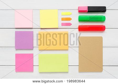 Flat lay of office and business stationery supplies - colorful markers, sticky notes and memo blocks on rustic wooden board background, top view with copy space