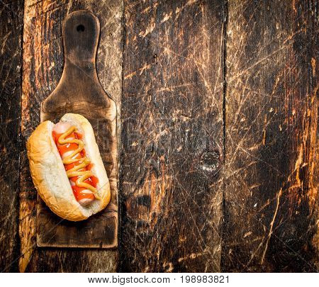 Hotdog With Mustard On The Old Board.