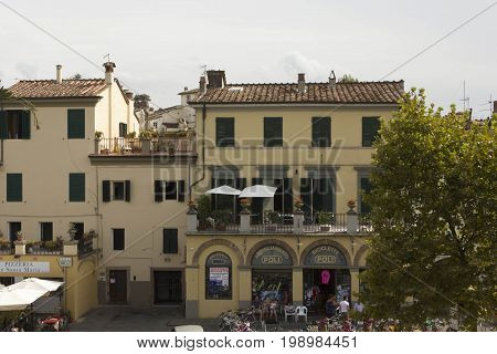 LUCCA, ITALY - AUGUSt 15 2015: Residential building in Lucca with the shops at the ground floor and people