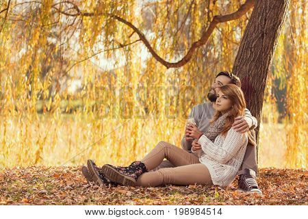 Couple in love sitting on autumn fallen leaves in a park enjoying a beautiful autumn day.