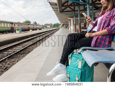 Young woman traveler and backpack waiting railway at train station, Young woman sitting with using smartphone at the train station, Summer holiday and travel concept.