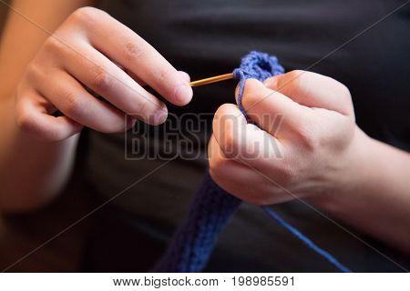 Closeup blue woolen  blue yarn female fingers