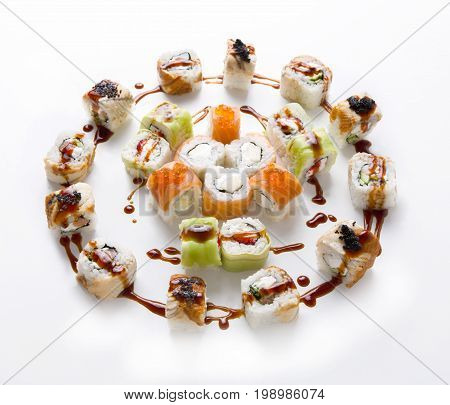 Colorful sushi set isolated at white background. Japanese restaurant food delivery and take away. Salmon, eel and vegetable rolls with philadelphia cheese and unagi sauce