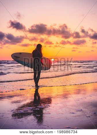 Silhouette of surfer girl with surfboard on a beach at sunset or sunrise. Surfer and ocean