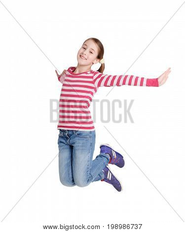 Happy girl jumping on white isolated background. Teenager in striped t-short and jeans smiling and posing. Active life and happy childhood concept