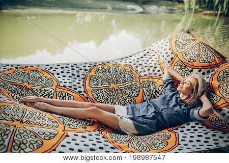 Smiling Blonde Hipster Woman Sleeping On A Hammock Outdoors, Beautiful Girl In Stylish Jean Clothing