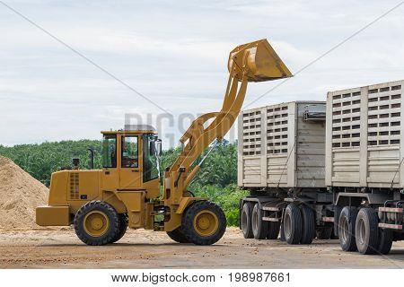 Bulldozer loading sand into the truck, Wheel loader excavator machine loading dumper truck at sand quarry