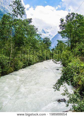 Interlaken, Switzerland On Cliff During Summer With Mountain Alpine River Or Creek