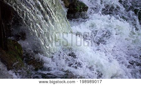 Powerful waterfall. Water flows and falls creating splashes and foam. Power and beauty in nature.