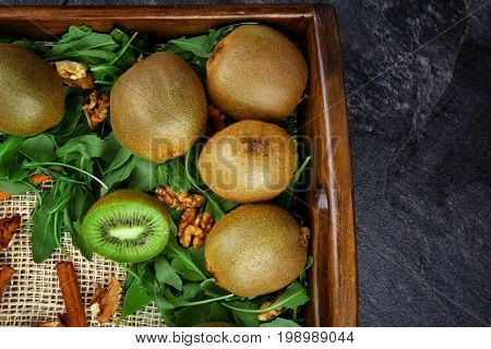 Close-up of an exotic kiwi on a gray stone background. Top view of a colorful kiwis, nuts and leaves in a crate. Summer fruits on a wooden tray. Copy space.