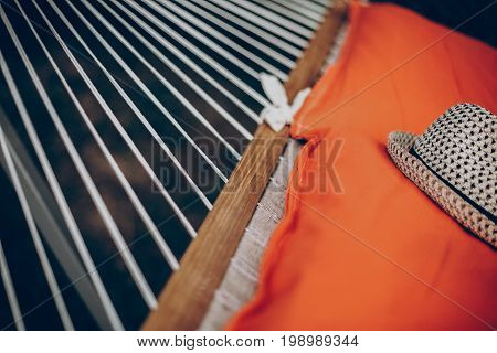 Comfortable orange hammock with a hat hanging outdoors in a park close-up boho hammock tied to trees camping concept