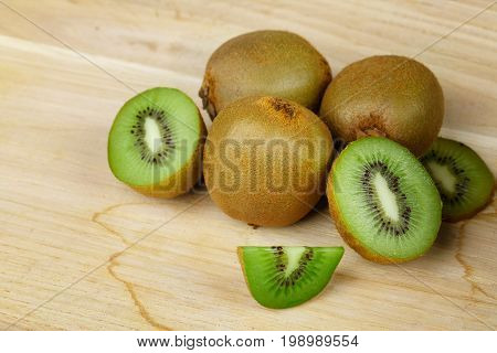 Closeup of a fresh heap of whole and cut in halves kiwi on a light wooden table. Slice of sappy kiwi, piled succulent kiwi on a light wooden table. An exotic summer fruits.
