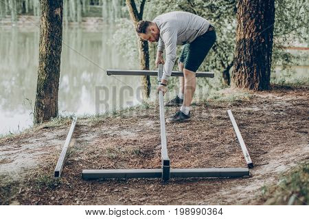 Strong handsome man constructing hammock support bars father putting together hammock for camping trip how to do it yourself concept