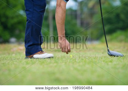 Playing golf, Golf club and ball, Preparing to shot, Lens flare on sun set evening time, Selective focus