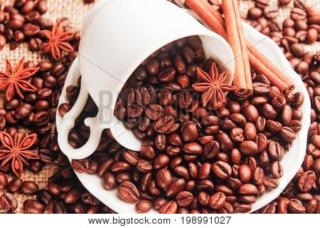 The white cup with a white saucer is overturned with coffee beans cinnamon and anise on sacking. Top view close-up