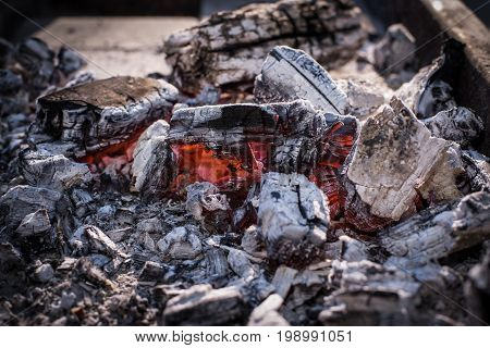 Hot coals are smoldering in the grill