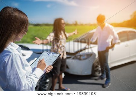 Insurance agent writing on clipboard after accident cars.