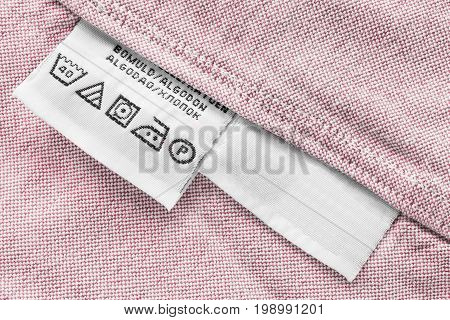 Washing instructions clothes label on pink cotton closeup