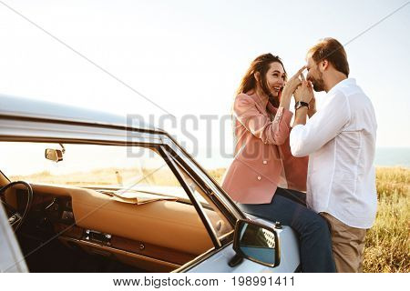 Happy playful couple in love leaning on a retro car outdoors