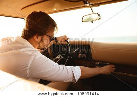 Young man driver turning on stereo system while sitting in a retro car with hand on a steering wheel