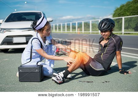 Female nurse helping emergency asia cyclist injured on the street bike after collision accident car and bike