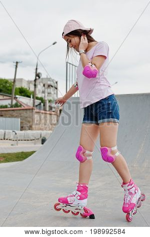 Good-looking Young Woman Wearing Cap, T-shirt And Shorts Pose In Rollerblades On The Skatepark.