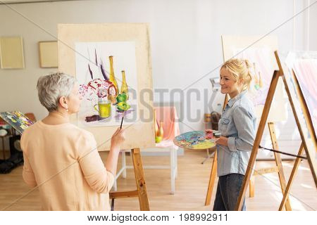 creativity, education and people concept - women artists painting still life picture on easels at art school studio and talking