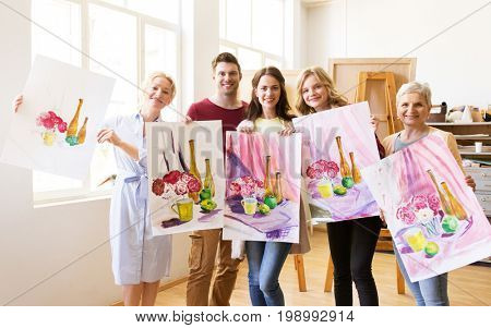 painting, education and people concept - group of artists or students holding still life pictures at art school studio