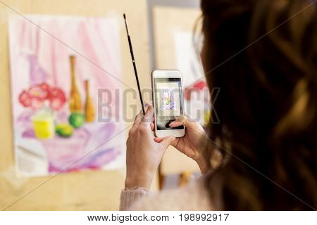 technologyl, creativity and people concept - woman artist or student with smartphone and brush photographing still life painting or picture at art school studio