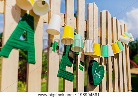 Garland fair bulbs. Summer. Wedding party decoration. Garland of paper cups hangs on wooden boards. Close-up