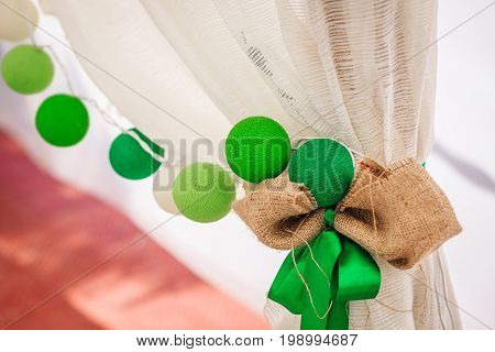 Cotton balls garland hangs on a white curtain. Bright colored decoration. Wedding outdoors