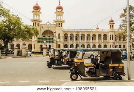 MYSORE, INDIA - FEB 20, 2017: Auto-rickshaws driving past structures of the public institutions in traditional indian architecture style on February 20, 2017. Mysore of Karnataka has a population of 900000
