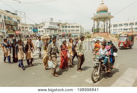 MYSORE, INDIA - FEB 20, 2017: Crowd of people walking cross the street with vehicles and pedestrians of indian city on February 20, 2017. Population of Karnataka is 62000000 people