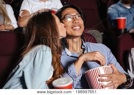 Image of young loving couple sitting in cinema watch film and kissing