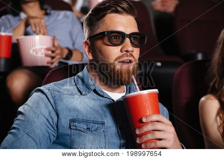 Photo of concentrated young man sitting in cinema watch film drinking aerated sweet water.