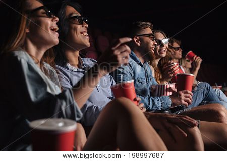 Image of young happy friends sitting in cinema watch film eating popcorn.