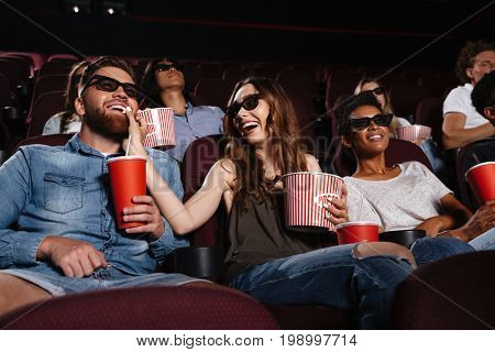 Photo of happy friends sitting in cinema watch film eating popcorn and drinking aerated sweet water.