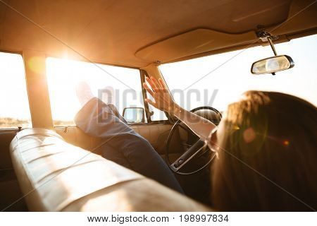 Young woman resting while lying on a front seat inside a car