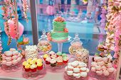 Candy Bar in pinky colors. Delicious sweet buffet with cupcakes and wedding cake. Sweet holiday buffet with marshmallows and other desserts. poster