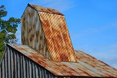 Rustic roof of the Ozark Diamond Mine's historic shaft house is framed by blue sky at the Crater of Diamonds State Park in Arkansas. poster