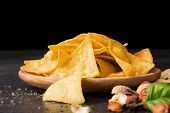 A close-up picture of gold nacho chips on a light wooden plate. Spicy snacks with salty peanuts, hazelnuts and green leaves. Mexican traditional appetizer on a saturated black background. Copy space. poster