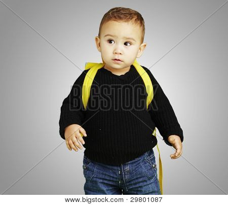 portrait of adorable kid carrying yellow backpack over grey background