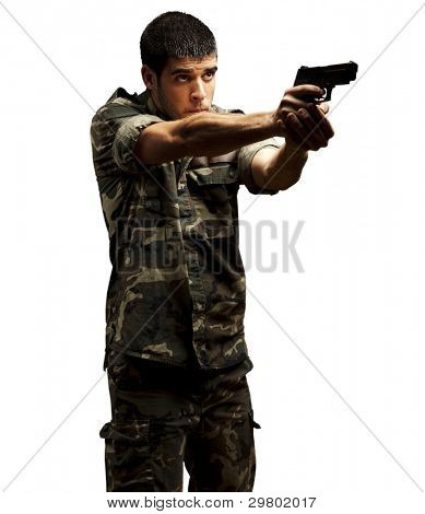 portrait of a young soldier aiming with pistol against a white background