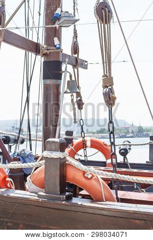 View on part of old wooden sailboat with bright sky background. Orange lifelines. Old deadeye with cables on the shrouds of a sailing ship in Varna, Bulgaria. poster