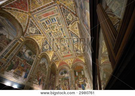 Interior of the Piccolomini library in the Siena Duomo cathedral showing the beautiful painted ceiling and frescoed walls. poster