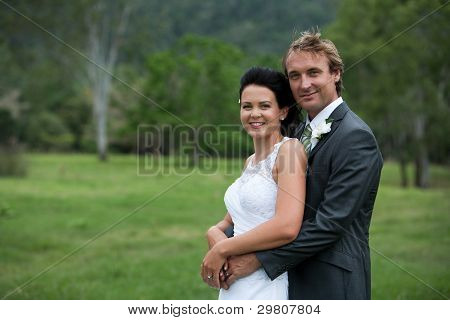 Bride And Groom Hugging In A Green Field