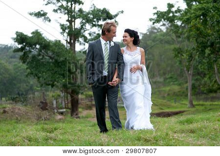 Bride And Groom Walking Hand In Hand In Rural Setting