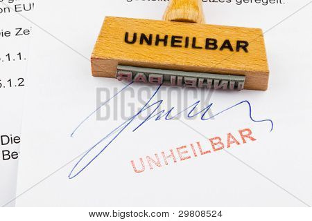 a stamp made of wood lying on a document. german inscription: incurable